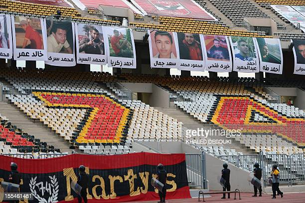 Egyptian policemen stand guard as portraits of the victims who died during the football match between Egyptian teams AlAhly and AlMasri at a stadium...