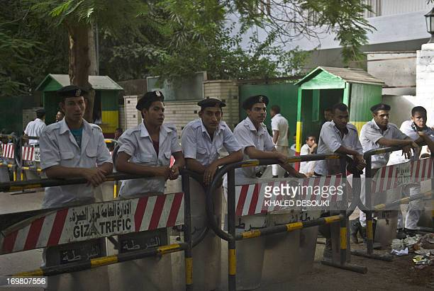 Egyptian policemen stand guard outside the Ethiopian embassy on June 2 2013 in Cairo as a dozen of protesters demonstrate in front of the building...