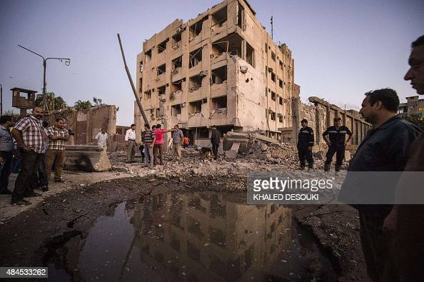 Egyptian policemen stand in front of a bombdamaged national security building in northern Cairo's district of Shubra on August 20 2015 A car bomb...