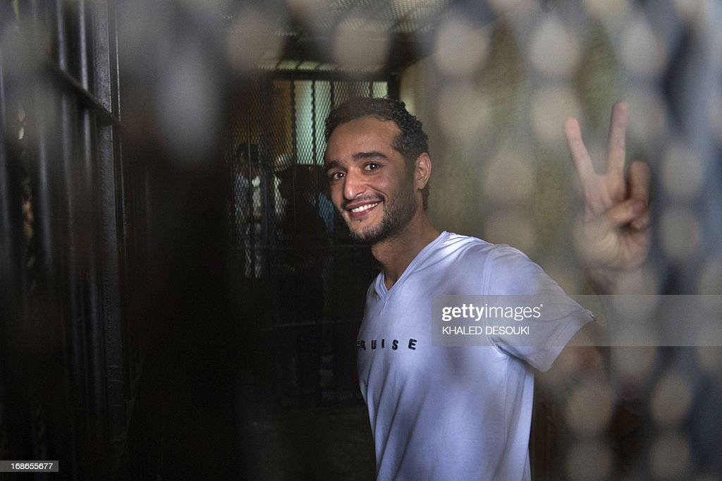 Egyptian political activist Ahmed Douma smiles and flashes the 'V' for victory sign as he stands behind dock bars during his trial in Cairo on May 13, 2013 on charges of insulting president Mohamed Morsi in a TV interview.