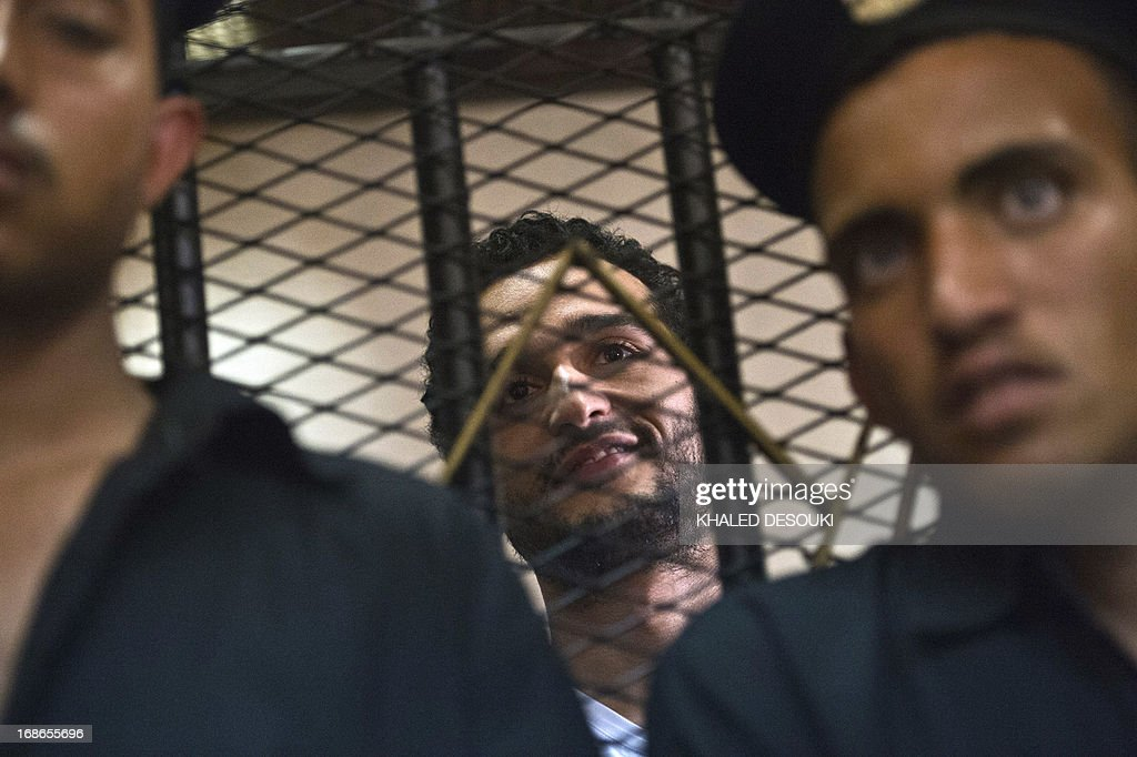 Egyptian political activist Ahmed Douma smiles as he stands behind dock bars during his trial in Cairo on May 13, 2013 on charges of insulting president Mohamed Morsi in a TV interview. AFP PHOTO / KHALED DESOUKI