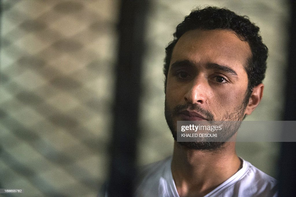 Egyptian political activist Ahmed Douma stands behind dock bars during his trial in Cairo on May 13, 2013 on charges of insulting president Mohamed Morsi in a TV interview. AFP PHOTO / KHALED DESOUKI