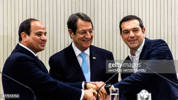 Egyptian President Abdel Fattah alSisi Cypriot President Nicos Anastasiades and Greek Prime Minister Alexis Tsipras all shake hands during a press...