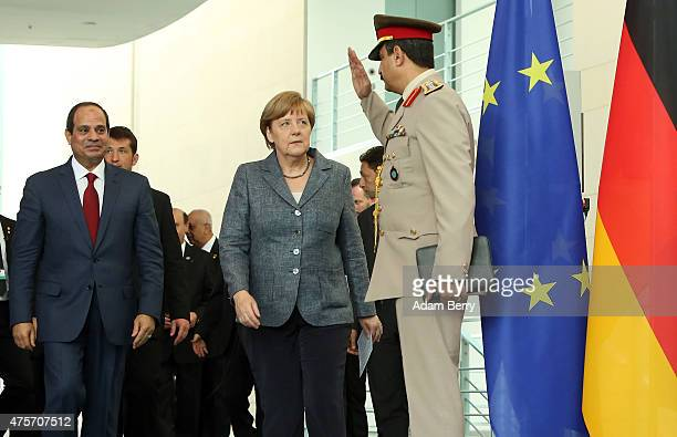 Egyptian President Abdel Fattah elSisi and German Chancellor Angela Merkel are saluted by an Egyptian military officer as they arrive for a news...