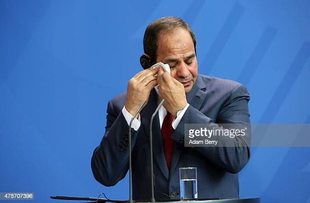 Egyptian President Abdel Fattah elSisi wipes his brow during a news conference with German Chancellor Angela Merkel on June 3 2015 in Berlin Germany...