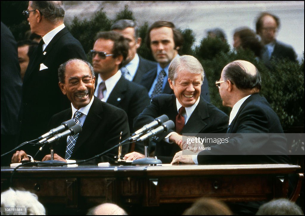 Egyptian President Anwar El Sadat (1918 - 1981) (left) smiles as he watches American President <a gi-track='captionPersonalityLinkClicked' href=/galleries/search?phrase=Jimmy+Carter+-+US+President&family=editorial&specificpeople=93589 ng-click='$event.stopPropagation()'>Jimmy Carter</a> (center) shakes the hand of Israeli Prime Minister <a gi-track='captionPersonalityLinkClicked' href=/galleries/search?phrase=Menachem+Begin&family=editorial&specificpeople=93758 ng-click='$event.stopPropagation()'>Menachem Begin</a> (1913 - 1992) after the signing of the Camp David Accords at the White House, Washington DC, March 26, 1979 1978.