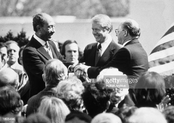 Egyptian president Anwar elSadat US president Jimmy Carter and Israeli prime minister Menachem Begin clasp their hands together following the signing...