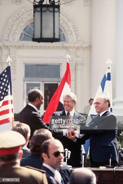 Egyptian president Anwar elSadat US President Jimmy Carter and Israeli Prime Minister Menachem Begin share a threeway handshake after signing an...