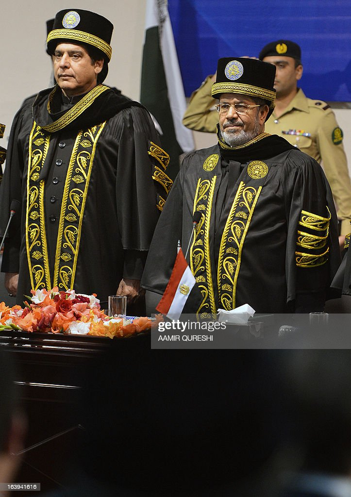 Egyptian President Mohamed Morsi (R) and Pakistani Prime Minister Raja Pervez Ashraf observe their national anthems during a special convocation at the National University of Science and Technology in Islamabad on March 18, 2013. Morsi arrived in Pakistan on March 18, on a South Asian tour that will also take in India as he works to promote trade and investment in his nation's troubled economy. Morsi's one-day trip to Pakistan is the first by an Egyptian leader since Gamal Abdel Nasser in the 1960s, Pakistan's foreign ministry said. AFP PHOTO/ AAMIR QURESHI