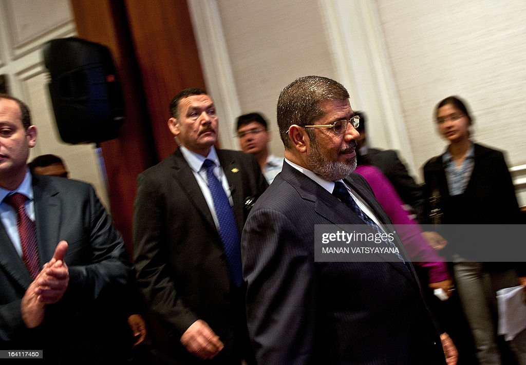 Egyptian President Mohamed Morsi (R) arrives to attend a business session in New Delhi on March 20, 2013. Egyptian President Mohamed Morsi called for an urgent halt to the 'bloodshed' in Syria after holding talks with Indian leaders in New Delhi.Morsi, who arrived in India late Monday for a two-day visit, told reporters that the global community must work together to end the 'bloodshed in Syria and find a peaceful solution'.