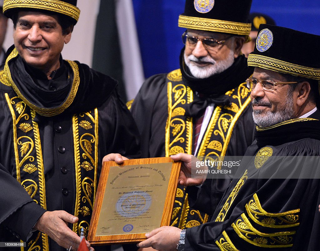 Egyptian President Mohamed Morsi (R) is conferred with an honourary doctor of philosophy from Pakistan's Prime Minister Raja Pervez Ashraf (L) during his visit to the National University of Science and Technology in Islamabad on March 18, 2013. Morsi arrived in Pakistan on March 18, on a South Asian tour that will also take in India as he works to promote trade and investment in his nation's troubled economy. Morsi's one-day trip to Pakistan is the first by an Egyptian leader since Gamal Abdel Nasser in the 1960s, Pakistan's foreign ministry said.