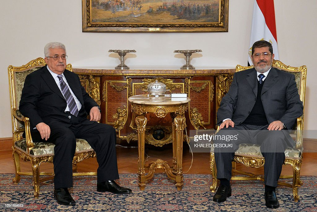 Egyptian President Mohamed Morsi (R) meets with Palestinian president Mahmud Abbas in Cairo on January 9, 2013. Abbas and Palestinian Hamas leader Khaled Meshaal are holding separate talks with Morsi before they meet each other to discuss the implementation of a unity pact signed in 2011, officials said.