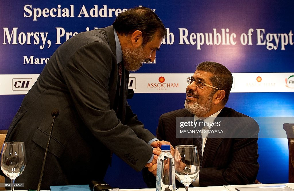 Egyptian President Mohamed Morsi (R) shakes hands with Indian Minister for Commerce, Industry and Textiles Anand Sharma during a India-Egypt Economic Forum in New Delhi on March 20, 2013. Egyptian President Mohamed Morsi called for an urgent halt to the 'bloodshed' in Syria after holding talks with Indian leaders in New Delhi.Morsi, who arrived in India late Monday for a two-day visit, told reporters that the global community must work together to end the 'bloodshed in Syria and find a peaceful solution'.