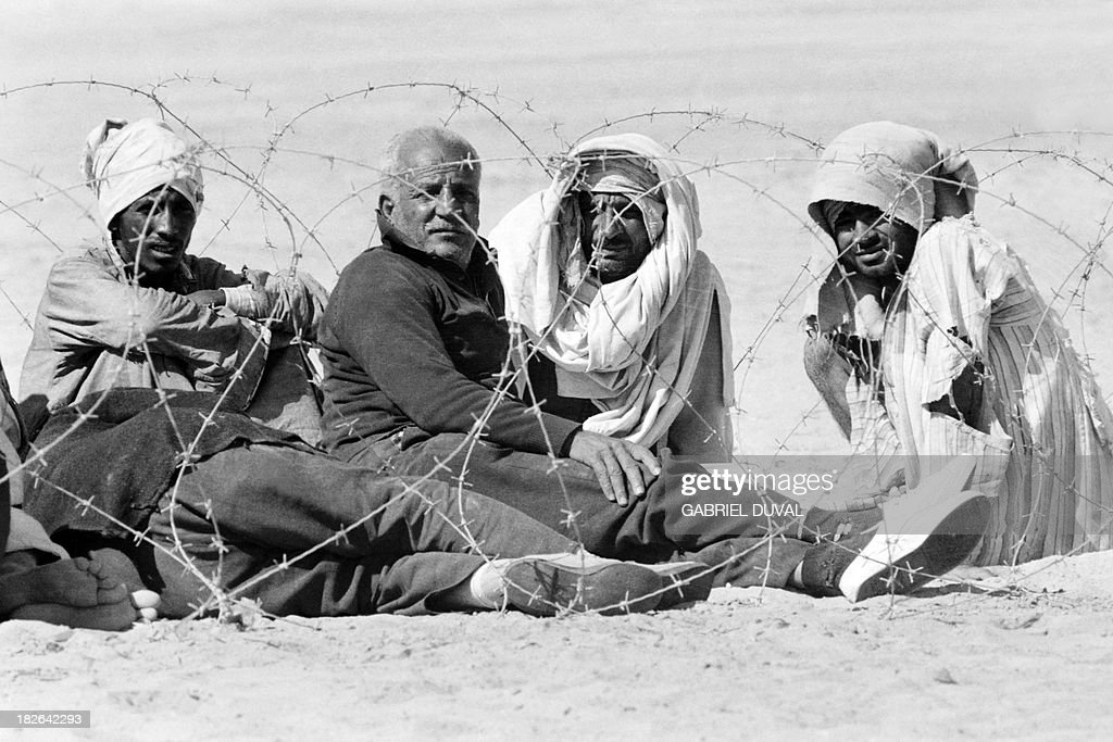 Egyptian prisonersofwar sit behind the barbed wire on November 01 1973 at a POW camp at the Suez canal less than a month after the beginning of the...