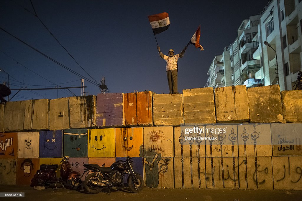 A Egyptian protester opposing president Mohammed Morsi waves Egyptian flags as he stands atop of a barricade securing the Presidential Palace prior to the start of a demonstration on December 18, 2012 in Cairo, Egypt. Hundreds of people gathered in front of the Presidential Palace and in Tahrir Square to protest against President Mohammed Morsi and the alleged rigging of the first round of voting in the constitutional referendum.