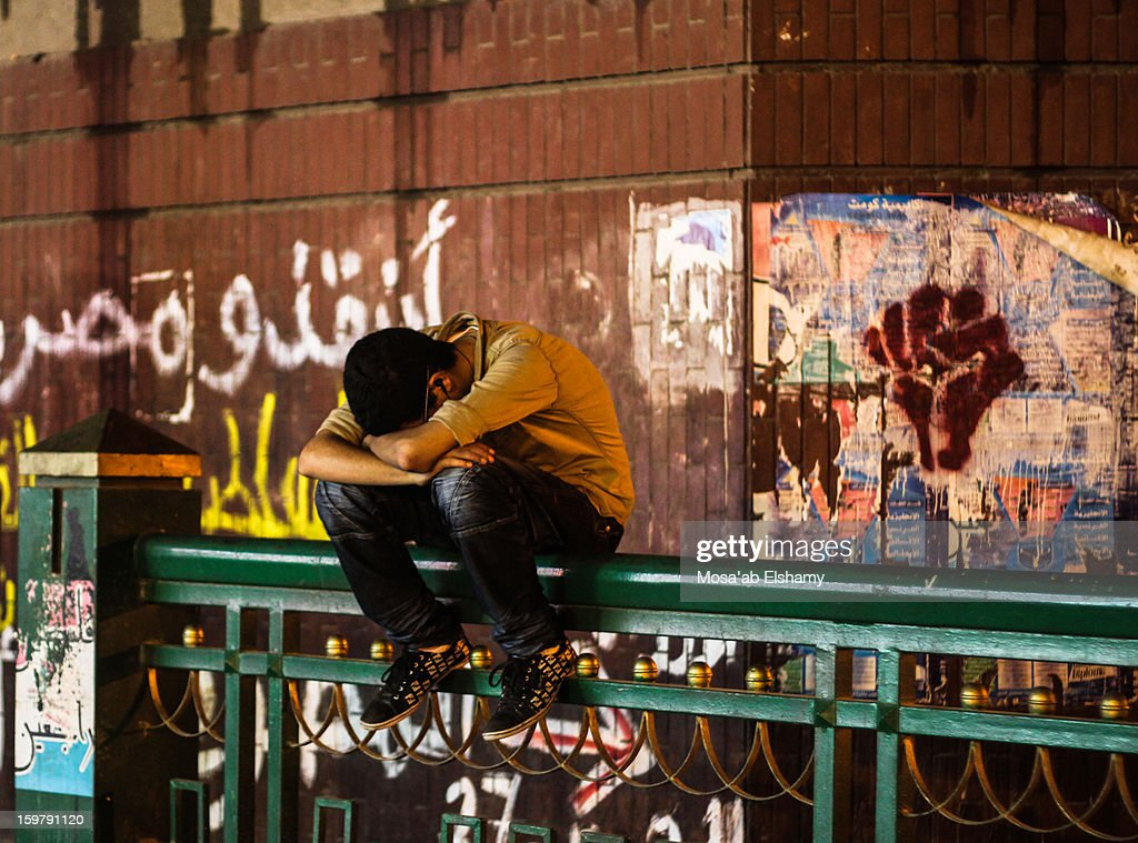 CONTENT] Egyptian protester rests in one of Tahrir entrances which he helps in securing for long shifts at night. On his right, 'Save Egypt' is written on the wall.