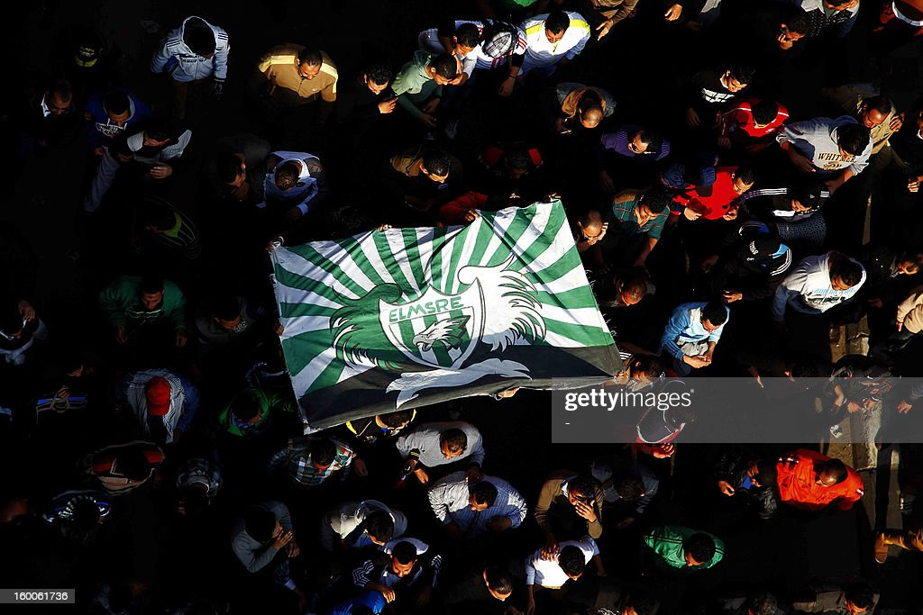 Egyptian protesters and fans of alMasry football club wave their club colours as they take part in a demonstration in front of the prison in the...