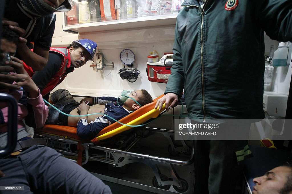 Egyptian protesters are treated in an ambulance after they inhaled tear gas used by riot police during a protest in Tahrir Square to call for the fall of Islamist President on January 24, 2012 in Cairo. Police clashed with protesters in Cairo earlier, on the eve of the the second anniversary of the uprising that overthrew Hosni Mubarak, as they tried to dismantle a security barrier and called for the fall of President Mohamed Morsi.