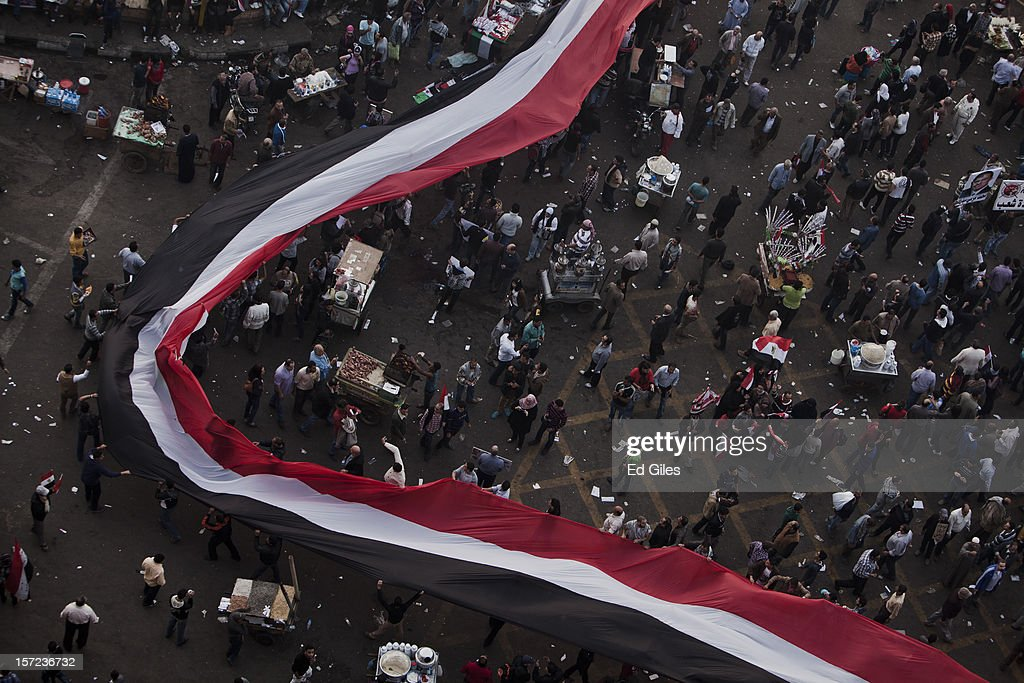 Egyptian protesters carry a giant Egyptian flag above their heads during a demonstration against Egyptian President Mohammed Morsi in Tahrir Square on Friday, November 30, 2012, in Cairo, Egypt. Demonstrations continue in Cairo today after Egypt's Constituent Assembly finalised a draft of the country's new constitution in an overnight voting session late on Thursday. Violent protests have continued for over ten days across the country in response to Egyptian president Mohammed Morsi having awarded himself new constitutional powers, which many believe have been pushed through by the Muslim Brotherhood without inclusive consultation with other members of Egypt's cabinet and political leadership. (Photo by Ed Giles/Getty Images).