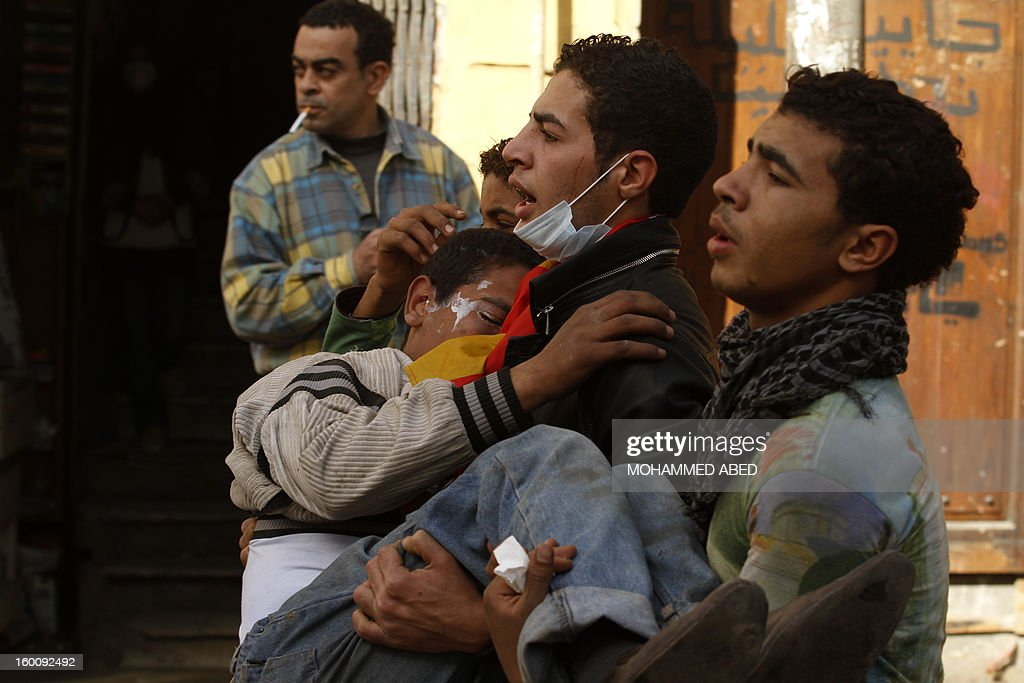 Egyptian protesters carry an injured boy during a demonsration in Cairo's Tahrir Square on January 26, 2013. Egypt's Islamist President Mohamed Morsi appealed for calm after at least seven people were killed in violence on the second anniversary of the revolution that ousted Hosni Mubarak.