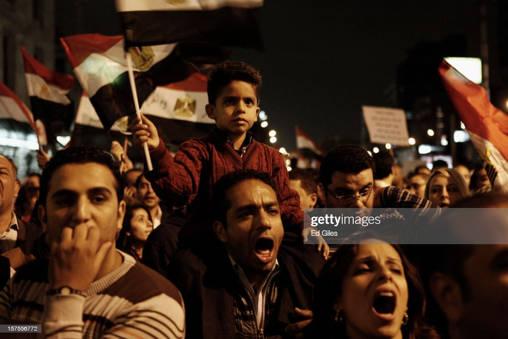 Egyptian protesters chant during a protest against Egyptian President Mohammed Morsi at the Presidential Palace on December 4 in in Cairo, Egypt. Thousands of protesters converged on the Presidential Palace in the Cairo suburb of Heliopolis on Tuesday evening to demonstrate against the country's draft constitution that was rushed through parliament in an overnight session on November 29. Protesters and police briefly clashed outside the Presidential Palace before riot police retreated inside the palace grounds. The country's new draft constitution, passed by a constitutional assembly dominated by Islamists, will go to a referendum on December 15.