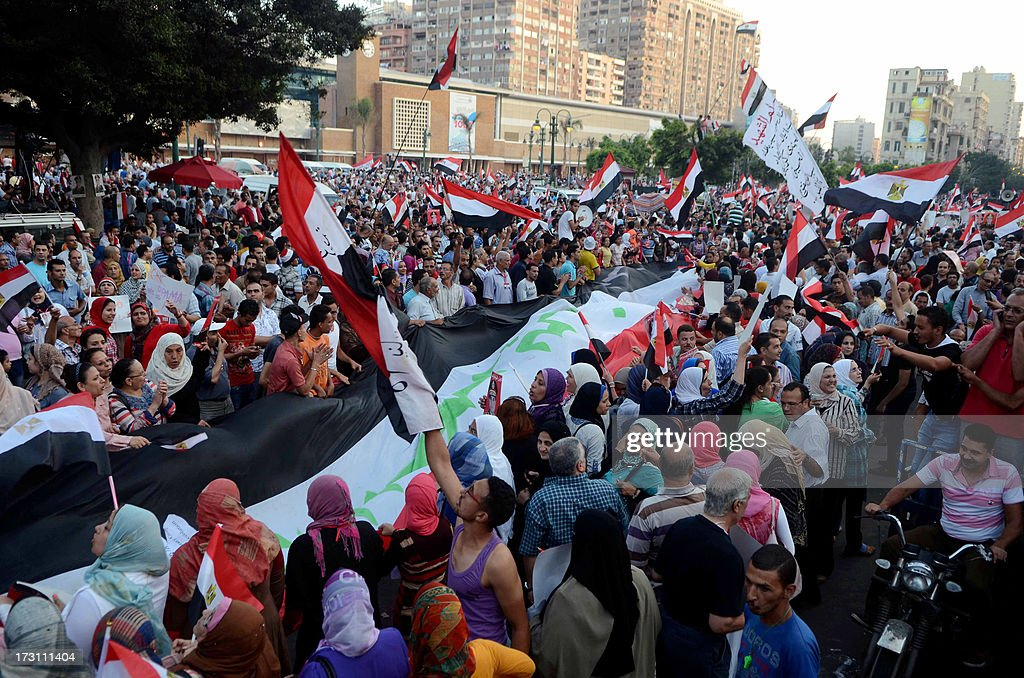 Egyptian protesters deploy a giant national flag during a demonstration against deposed President Mohamed Morsi on July 7, 2013 in the northern Egyptian city of Alexandria. In the capital, opponents of Morsi packed Tahrir Square in their tens of thousands to show the world his ouster was not a military coup but the reflection of the people's will.