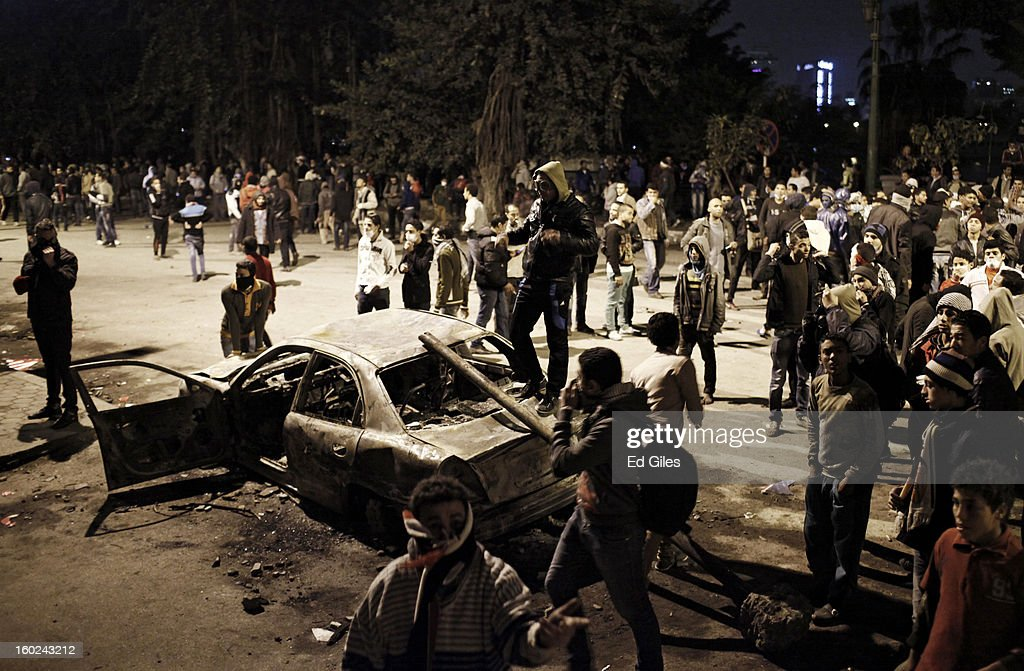 Egyptian protesters gather around the burnt-out wreck of a car during clashes between protesters and Egyptian riot police near Tahrir Square on January 28, 2013 in Cairo, Egypt. Violent protests continued across Egypt three days after the second anniversary of the Egyptian Revolution that overthrew former President Hosni Mubarak and two days after 21 men were sentenced to death in connection with the deaths of 74 football fans during riots at Port Said stadium one year ago.