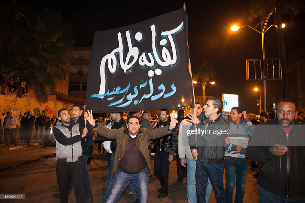 Egyptian protesters gather in the streets of Port Said late on January 29, 2013 in defiance of the curfew imposed by President Mohamed Morsi. The army is already deployed in the city of Port Said, 220 kms northeast of Cairo, where the worst of the bloodshed occurred in rioting triggered by death sentences passed on 21 supporters of a local football club over deadly soccer riots last year. Placard in Arabic reads: 'Enough injustice. The state of Port Said.'