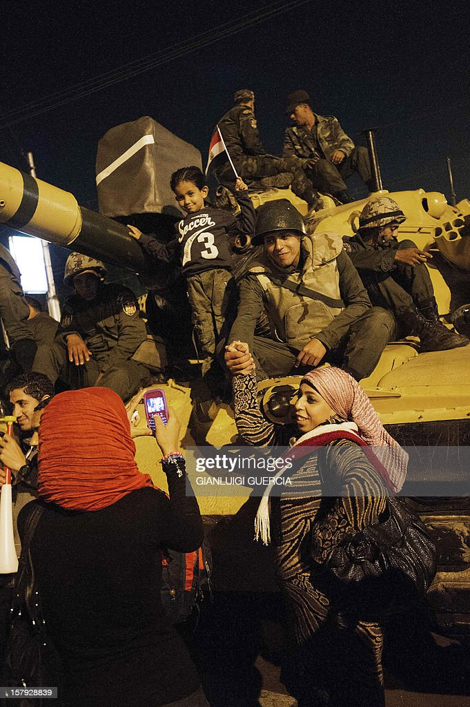 Egyptian protesters have their picture taken and shake hands with Egyptian army soldiers standing on top of an army tank as thousands of protesters walk in the streets in front of the presidential palace on December 7, 2012 in Cairo. Thousands of protesters broke through a barbed-wire perimeter protecting President Mohamed Morsi's palace, as his vice-president hinted at a possible compromise aimed at calming the seething crisis dividing Egypt. AFP PHOTO/GIANLUIGI GUERCIA