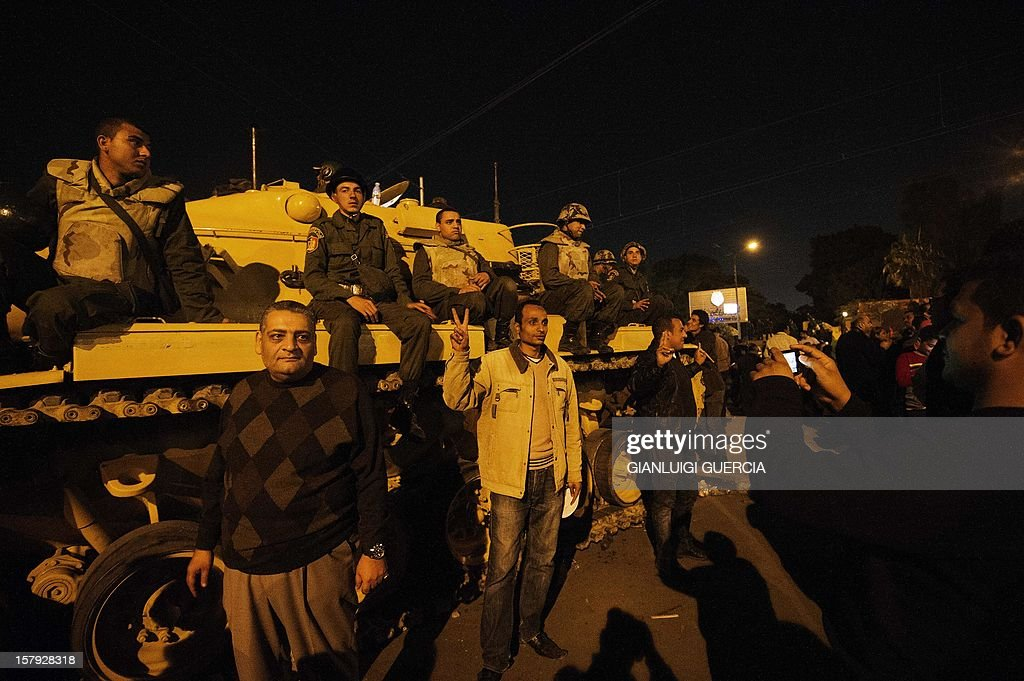 Egyptian protesters have their picture taken posing with Egyptian army soldiers as thousands of opponents to Egyptian President Mohammed Morsi gather in front of the palace on December 7, 2012 in Cairo. Thousands of protesters broke through a barbed-wire perimeter protecting Morsi's palace, as his vice-president hinted at a possible compromise aimed at calming the seething crisis dividing Egypt. AFP PHOTO/GIANLUIGI GUERCIA