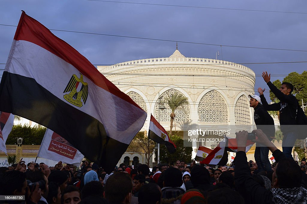 Egyptian protesters holds flags during a demonstration in opposition to Morsi and his Muslim Brotherhood in front of the Presidential palace in Cairo on February 1, 2013. Egyptian security used water cannon and fired shots into the air as protesters threw petrol bombs and stones into the grounds of the presidential palace, an AFP correspondent said.