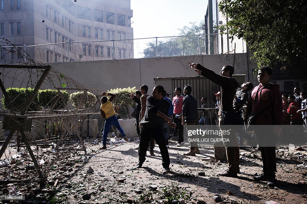 Egyptian protesters hurl stones towards Egyptian riot Police during clashes at Simon Bolivar square on November 25, 2012 in Cairo. Egypt's powerful Muslim Brotherhood called nationwide demonstrations today in support of Islamist President Mohamed Morsi in his showdown with the judges over the path to a new constitution.