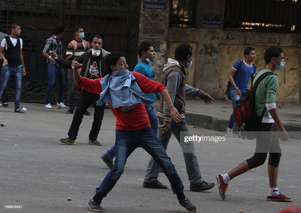 Egyptian protesters hurl stones towards Egyptian riot Police during clashes at Tahrir square on November 25, 2012 in Cairo. Egypt's powerful Muslim Brotherhood called nationwide demonstrations today in support of Islamist President Mohamed Morsi in his showdown with the judges over the path to a new constitution. AFP PHOTO
