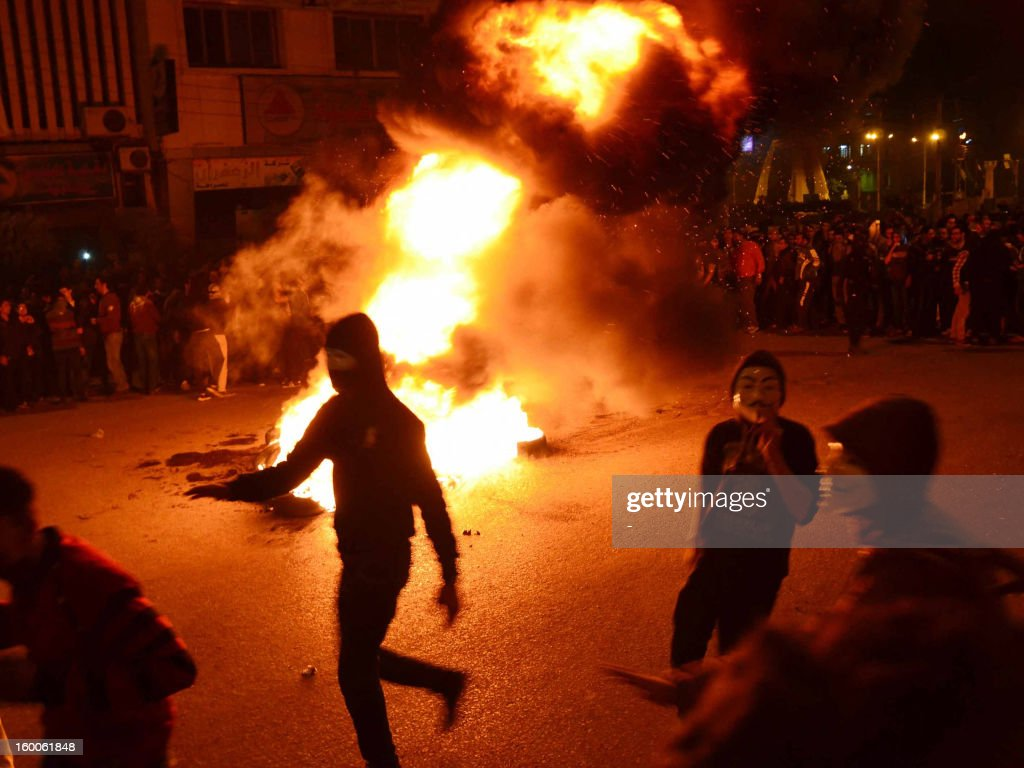 Egyptian protesters light a fire in the street in the Nile Delta city of Mansura some 120 kilometres north of Cairo on January 25, 2013. Protesters stormed a regional government headquarters in Cairo and clashed with police as mass rallies shook Egypt on the second anniversary of a revolt that ousted Hosni Mubarak and brought Islamists to power. AFP PHOTO / STR