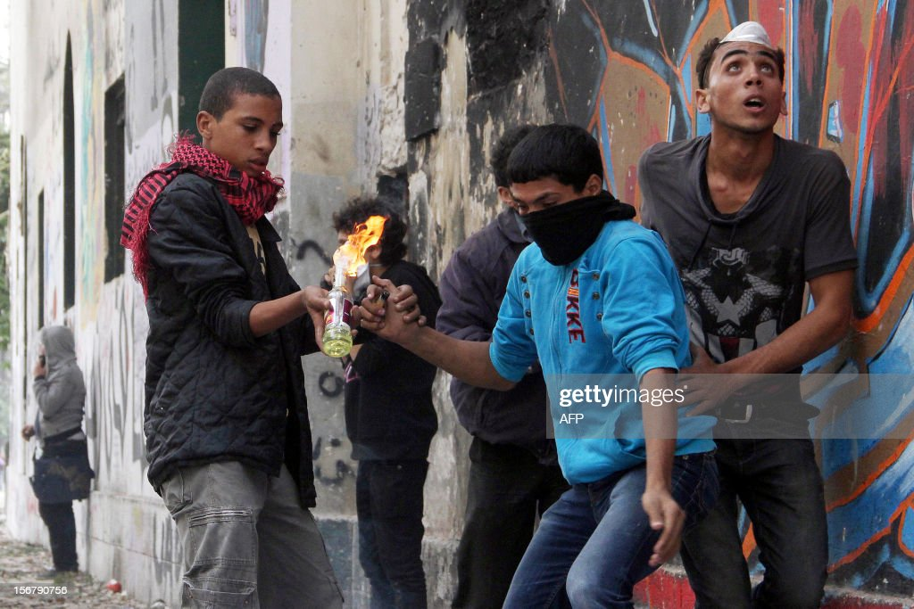 Egyptian protesters light a Molotov cocktail during clashes in Cairo on November 21, 2012. Egyptian protesters clashed with the police for a third day on the one year anniversary of deadly clashes that left 45 dead. At least 45 protesters died in the five days of street battles that began on November 19 last year to put pressure on the military, which took power after a popular uprising overthrew president Hosni Mubarak in February.