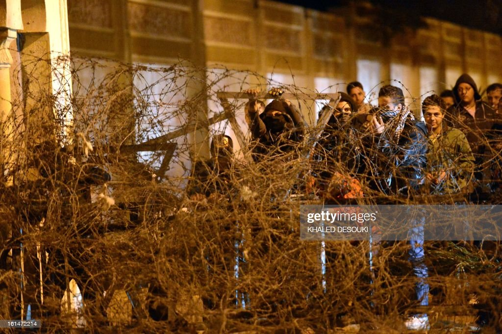 Egyptian protesters, members of the Black Bloc group, try to pull down a barbed wire barrier placed in front of the presidential palace in Cairo, on February 11, 2013, during opposition held rallies to mark the second anniversary of former president Hosni Mubarak's overthrow.