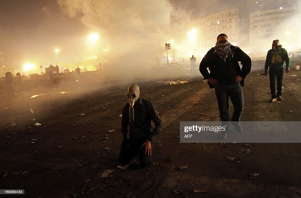 Egyptian protesters recover from tear gas fired by riot police in Cairo's Tahrir Square on January 25, 2013. Protesters stormed a regional government headquarters and clashed with police as mass rallies shook Egypt on the second anniversary of a revolt that ousted Hosni Mubarak and brought Islamists to power.