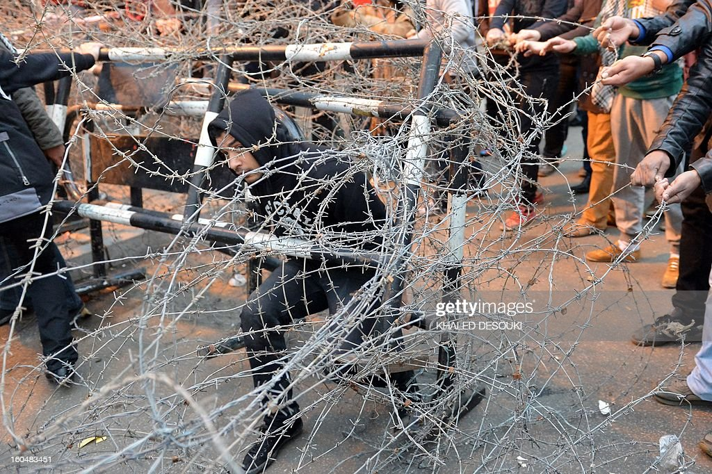 Egyptian protesters remove barbed wire during a demonstration in a show of opposition to Morsi and his Muslim Brotherhood in front of the Presidential palace in Cairo on February 1, 2013. Egyptian security used water cannon and fired shots into the air as protesters threw petrol bombs and stones into the grounds of the presidential palace, an AFP correspondent said.