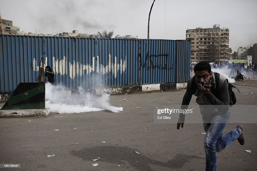 Egyptian protesters run away from tear gas canisters fired by riot police during a demonstration in Tahrir Square on January 27, 2013 in Cairo, Egypt. Violent protests continued across Egypt two days after the second anniversary of the Egyptian Revolution that overthrew former President Hosni Mubarak on January 25, and one day after the announcement of the death penalty for 21 suspects in connection with a football stadium massacre one year before. The verdict was announced in a case over the deaths of more than seventy fans of Egypt's Al-Ahly football club in a stadium massacre on February 1, 2012, in the northern city of Port Said, during a brawl that began minutes after the final whistle of a match between Al-Ahly and opposing side, Al-Masry. 21 fans of the opposing side, Al-Masry, were given the death penalty, a verdict that must now be approved by Egypt's Grand Mufti. (Photo by Ed Giles/Getty Images).