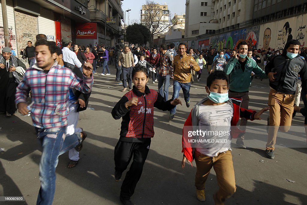Egyptian protesters run for cover after throwing stones towards riot police during a demonstration in Cairo's Tahrir Square on January 26, 2013. Egypt's Islamist President Mohamed Morsi appealed for calm after at least seven people were killed in violence on the second anniversary of the revolution that ousted Hosni Mubarak. AFP PHOTO/MOHAMMED ABED