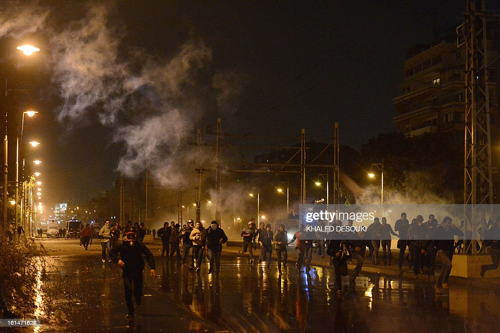 Egyptian protesters run for cover as tear gas is fired by riot police at stone-throwing protesters in front of the presidential palace in Cairo, on February 11, 2013, during opposition held rallies to mark the second anniversary of former president Hosni Mubarak's overthrow.