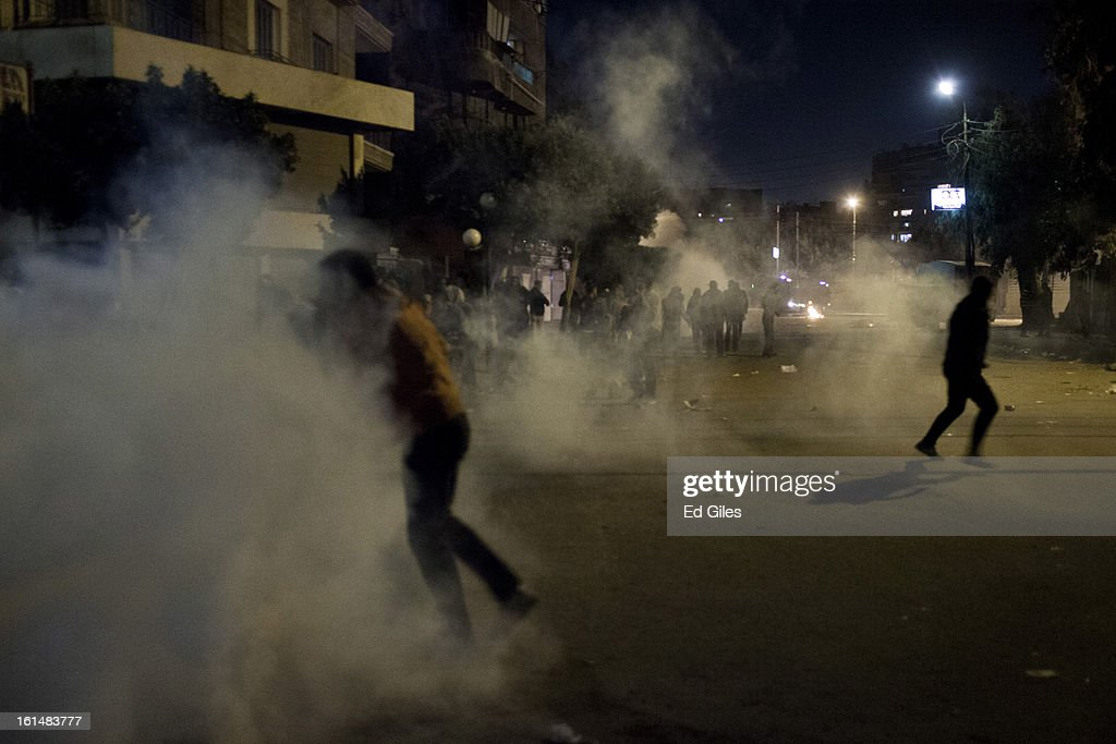 Egyptian protesters run through clouds of tear gas fired by Egyptian riot police during violent protests by the Presidential Palace in Heliopolis, February 11, 2013 in Cairo, Egypt. Protests continued across Egypt against President Morsi and the Muslim Brotherhood on the 2nd anniversary of former President Hosni Mubarak stepping down, and over two weeks after the second anniversary of the Egyptian Revolution beginning on January 25, 2011. (Photo by Ed Giles/Getty Images).