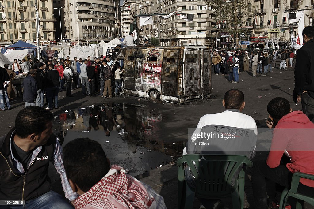 Egyptian protesters stand by a destroyed armoured vehicle of the Egyptian Central Security Forces stolen and burnt in earlier clashes between protesters and riot police nearby, in Tahrir Square on January 31, 2013 in Cairo, Egypt. Protests continued across Egypt nearly one week after the second anniversary of the Egyptian Revolution that overthrew former President Hosni Mubarak on January 25, 2011. Further protests are expected over the coming weekend to commemorate the first anniversary of the Port Said football massacre, when over 70 fans of the Cairo-based Al Ahly football club were killed in a violent post-match brawl between fans of the opposing teams inside the Port Said football stadium after a match between the Al Ahly and Al Masry football teams.