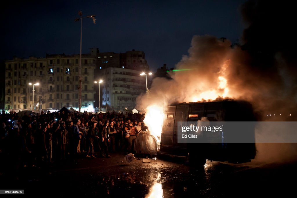 Egyptian protesters stand by an armoured Egyptian riot police vehicle of the, or Central Security Forces, that had been stolen then set alight during clashes nearby, in Tahrir Square on January 28, 2013 in Cairo, Egypt. Violent protests continued across Egypt three days after the second anniversary of the Egyptian Revolution that overthrew former President Hosni Mubarak and two days after 21 men sentenced to death in connection with the deaths of 74 football fans during riots at Port Said stadium one year ago.