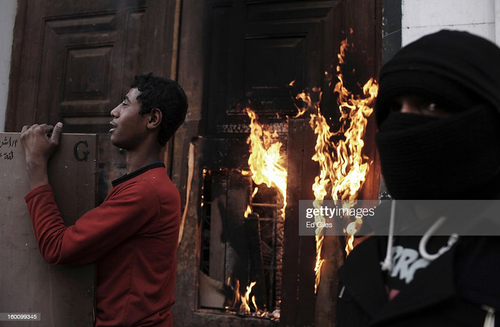 Egyptian protesters stand by the burning door of a school building during a protest following the announcement of the death penalty for 21 suspects in connection with a football stadium massacre last year, on January 26, in Cairo, Egypt. Protests have continued across Egypt after a verdict was announced in a case over the deaths of more than seventy fans of Egypt's Al-Ahly football club in a stadium massacre on February 1, 2012, in the northern city of Port Said, during a brawl that began minutes after the final whistle of a match between Al-Ahly and opposing side, Al-Masry. 21 fans of the opposing side, Al-Masry, were given the death penalty in the court case, a verdict that must now be approved by Egypt's Grand Mufti. The verdict was handed down during a period of high tension across Egypt, one day after the second anniversary of the beginning of Egypt's 2011 revolution that overthrew former President, Hosni Mubarak.