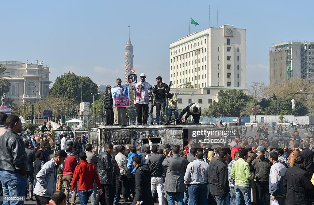 Egyptian protesters stand on a burnt-out police vehicle in Cairo's Tahrir Square on January 29, 2013. Egypt's military chief warned that the political crisis sweeping the country could lead to the collapse of the state, as thousands defied curfews and the death toll from days of rioting rose to 52.