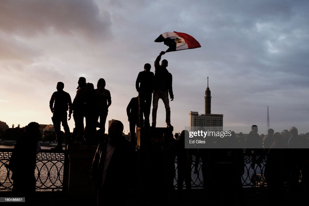 Egyptian protesters stand on a fence by the Nile River during a protest against Egyptian President Mohammed Morsi near Tahrir Square on February 1, 2013 in Cairo, Egypt. Protests continued across Egypt nearly one week after the second anniversary of the Egyptian Revolution that overthrew former President Hosni Mubarak on January 25, 2011. Further protests are expected Friday to commemorate the first anniversary of the Port Said football massacre, when over 70 fans of the Cairo-based Al Ahly football club were killed in a violent post-match brawl between fans of the opposing teams inside the Port Said football stadium after a match between the Al Ahly and Al Masry football teams.