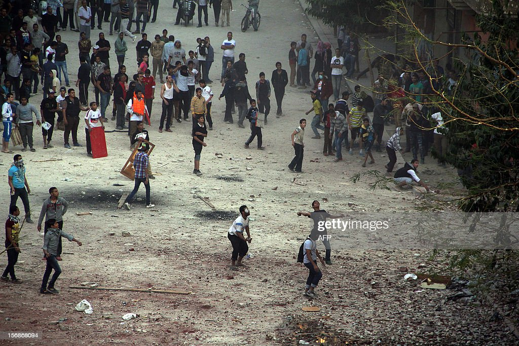 Egyptian protesters throw rocks towards Egyptian riot police during clashes following a demonstration against Egypt's Islamist President Mohamed Morsi in Cairo's landmark Tahrir square on November 23, 2012. Protesters set fire to Muslim Brotherhood offices, state television reported, as rival rallies were held nationwide a day after Morsi assumed sweeping powers.