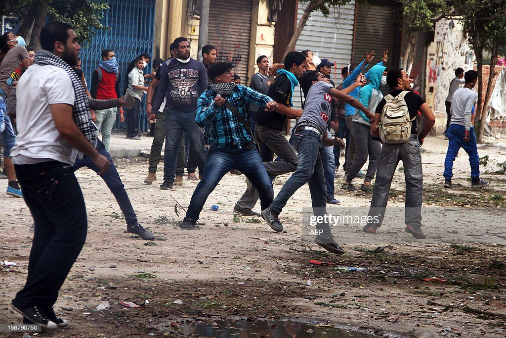 Egyptian protesters throw stones towards Egyptian security forces during clashes in Cairo on November 21, 2012. Egyptian protesters clashed with the police for a third day on the one year anniversary of deadly clashes that left 45 dead. At least 45 protesters died in the five days of street battles that began on November 19 last year to put pressure on the military, which took power after a popular uprising overthrew president Hosni Mubarak in February.