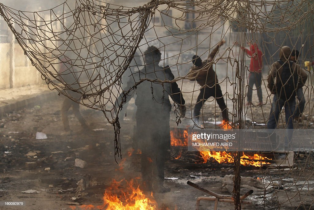 Egyptian protesters throw stones towards riot police during a demonstration in Cairo's Tahrir Square on January 26, 2013. Egypt's Islamist President Mohamed Morsi appealed for calm after at least seven people were killed in violence on the second anniversary of the revolution that ousted Hosni Mubarak.